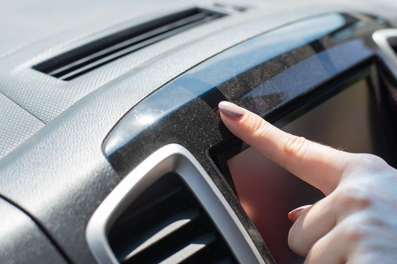 Wiping dust off a car dashboard. Dust reppelents for cars,